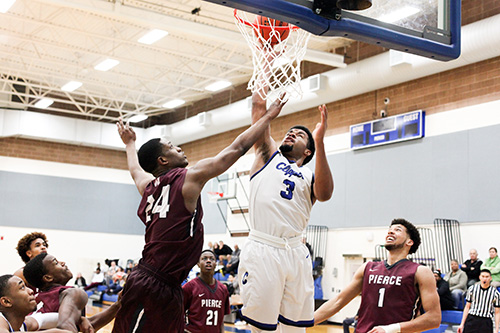 SPSCC's DeMonte Malloy shoots a layup past two onlookers from Pierce College