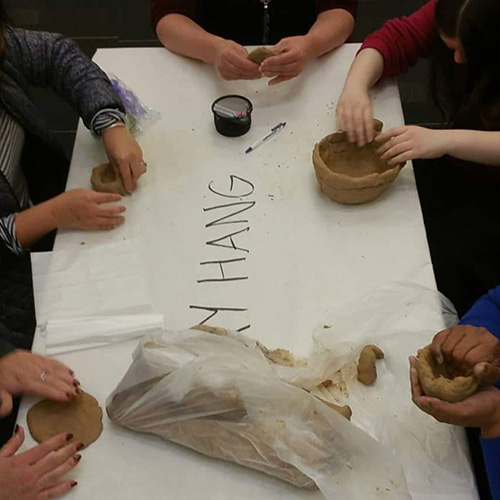 "A group of students sit at a table labeled ""CLAY HANG"", working with clay and fashioning cups and bowls"