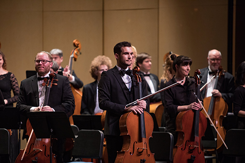 Male cellist in a black suit and bowtie standing before the performance begins