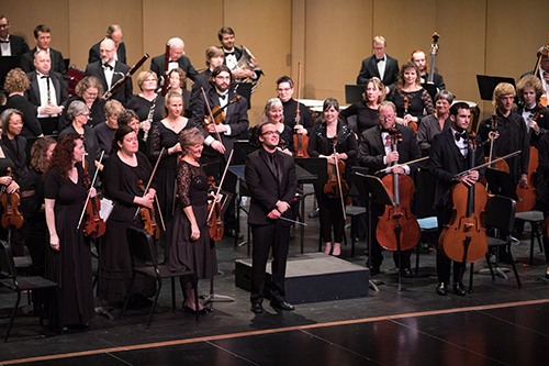 The SPSCC orchestra rises from their seats, with conductor Cameron May standing at their front