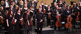 Thumbnail: The SPSCC orchestra rises from their seats, with conductor Cameron May standing at their front
