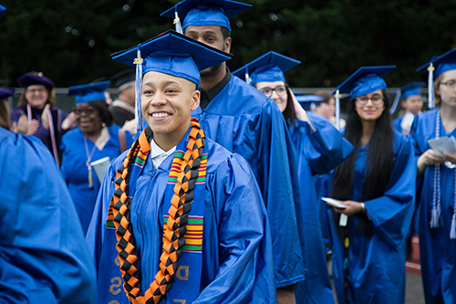 A group of smiling SPSCC students wearing ceremonial blue mortarboard cap and gown