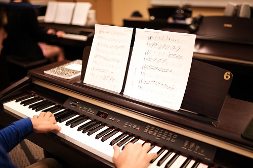 Hands on keyboard keys with sheet music on a stand