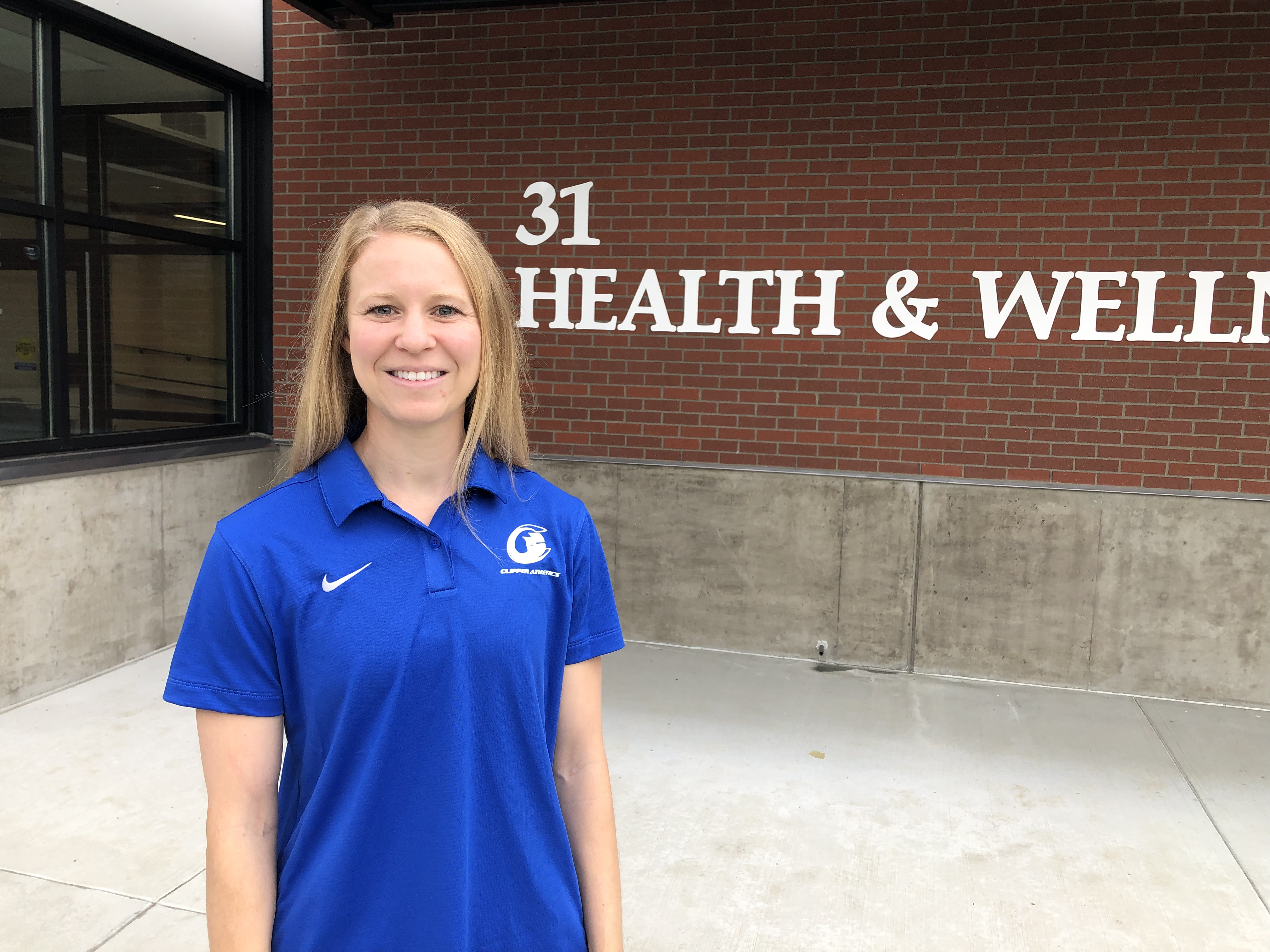 Coach Mader smiles in a blue Clipper Athletics polo outside of the Health & Wellness Center (Bldg. 31)