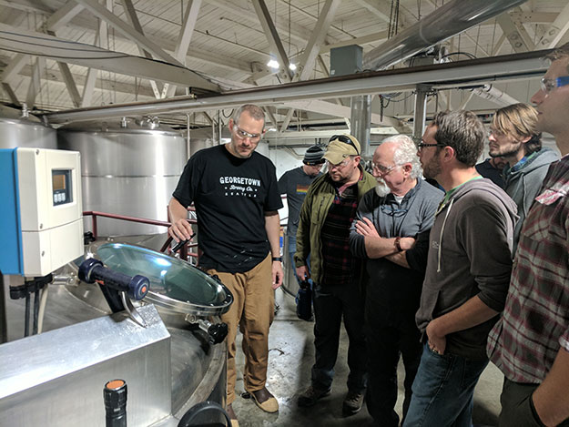 Adult students look at brewing equipment in warehouse setting