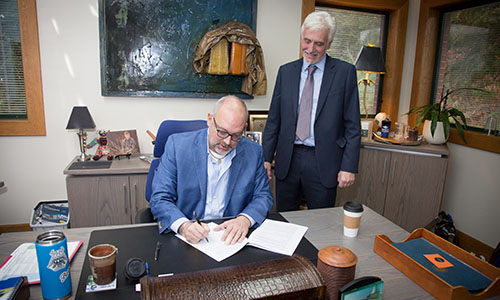 SPSCC President Dr. Tim Stokes signing a stack of papers at his desk, with Dr. Iain Johnstone of University of Glasgow overseeing