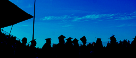 graduates with caps on in silhouette with blue sky and stadium backgroud