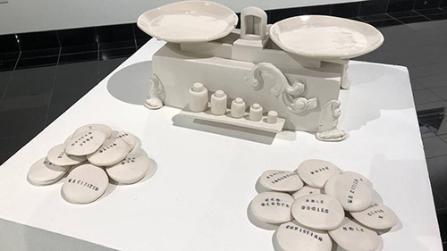 """Gugliotti's """"Weight of Privilege"""", a set of circular ceramic stones engraved with privileges and accompanying ceramic scales"""