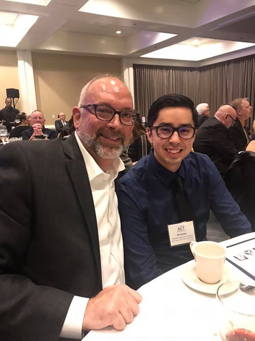 SPSCC President Dr. Tim Stokes attends the awards dinner alongside Eli Cortes, a smiling, bespectacled young man with dark hair
