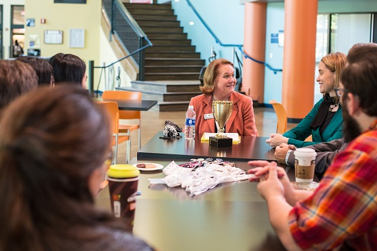 Mary Hall smiles with trophy and students around the table