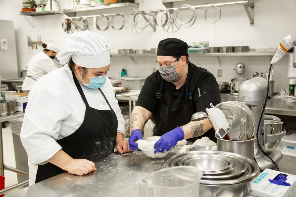 Two culinary arts students prepping food