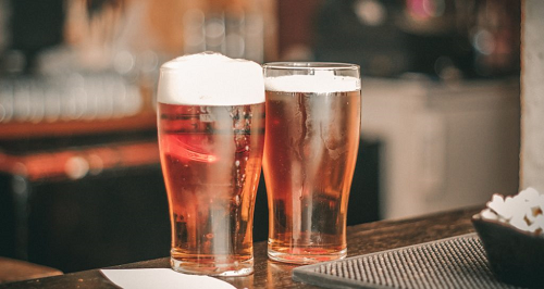 A close up of two beers on a bartop