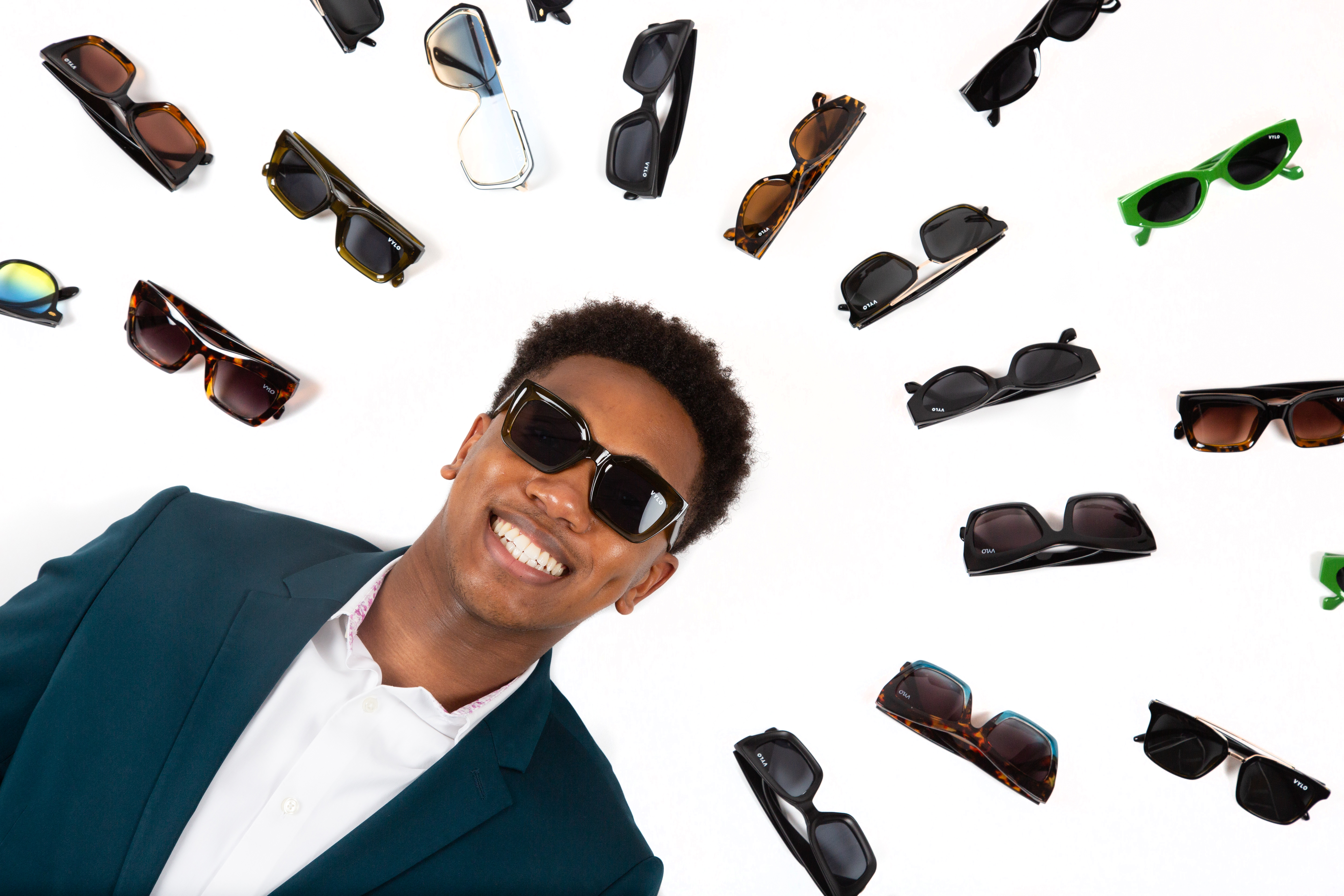 Tyser, from chest up, lays down with an array of sunglass styles displayed around his head