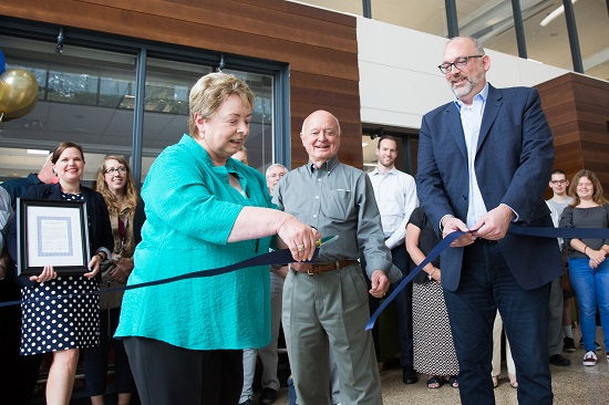 West Olympia Rotary member cuts blue ribbon with a crowd onlooking, including SPSCC president Tim Stokes and Foundation executive director Tanya Mote