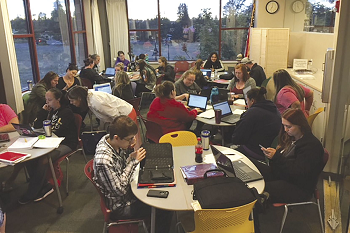 Large group of HS21+ students studying at tables in a room at Yelm High School