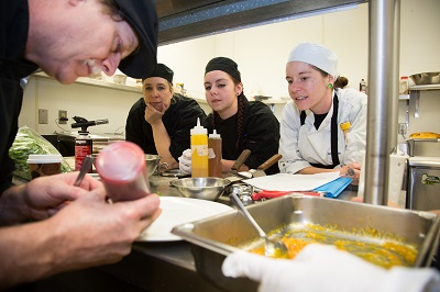 Chef garnishes a plate with three onlooking students