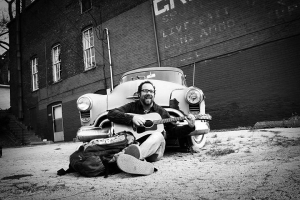 Andy with guitar sitting in front of a car
