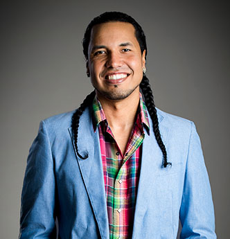 Gyasi Ross, a Native American man in a light blue suit and dark, braided hair, smiling