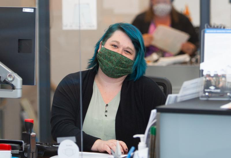 staff member smiles from desk with mask