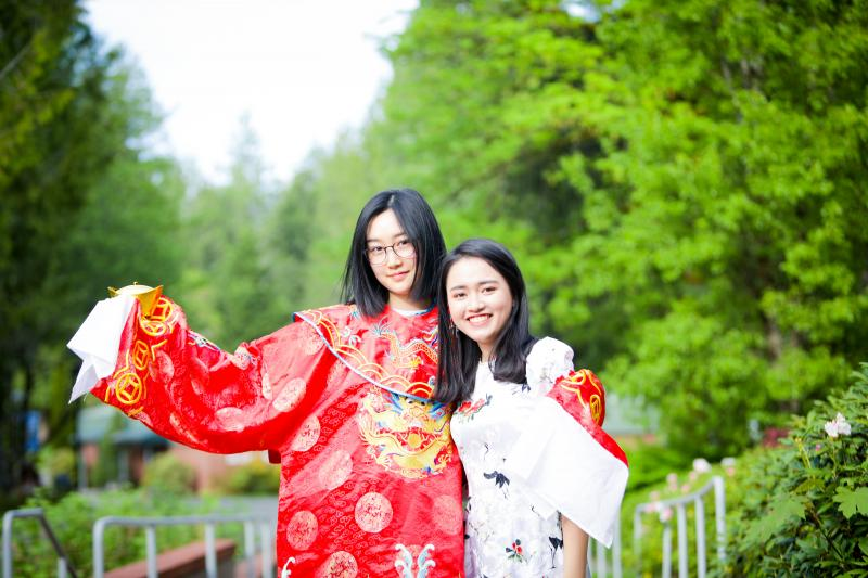 Two international students smile in traditional dress with green trees