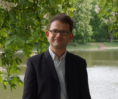 Man Jacek Nazarczuk with glasses smiling at camera in front of lake a green tree