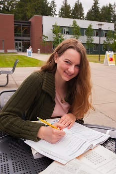 Female student sitting in quad while studying textbook