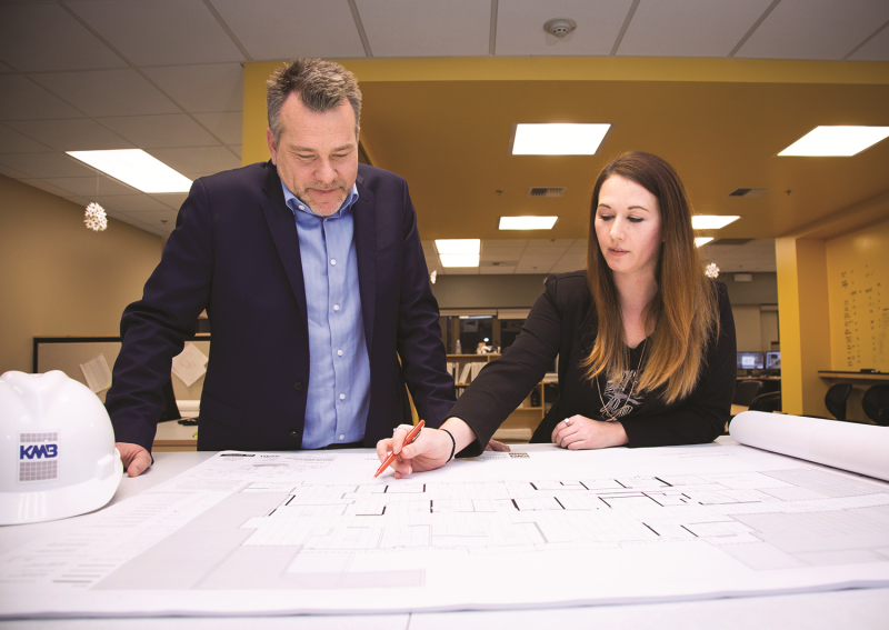 Mark and Elizabeth review printed architectural drawings
