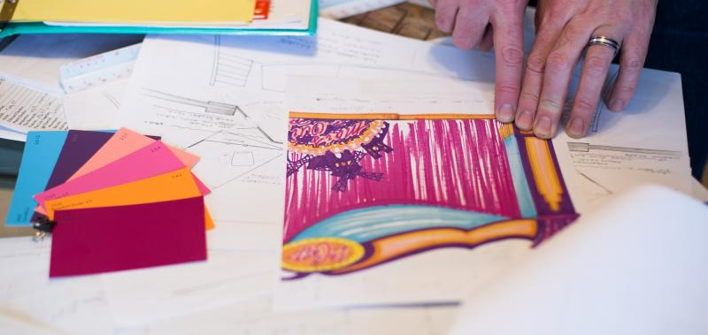 Fingers pointing at set design sketch with bright pink colors