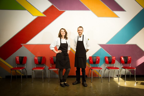 Marilyn and Brad stand in front of a colorful wall and restaurant table in black aprons, smiling