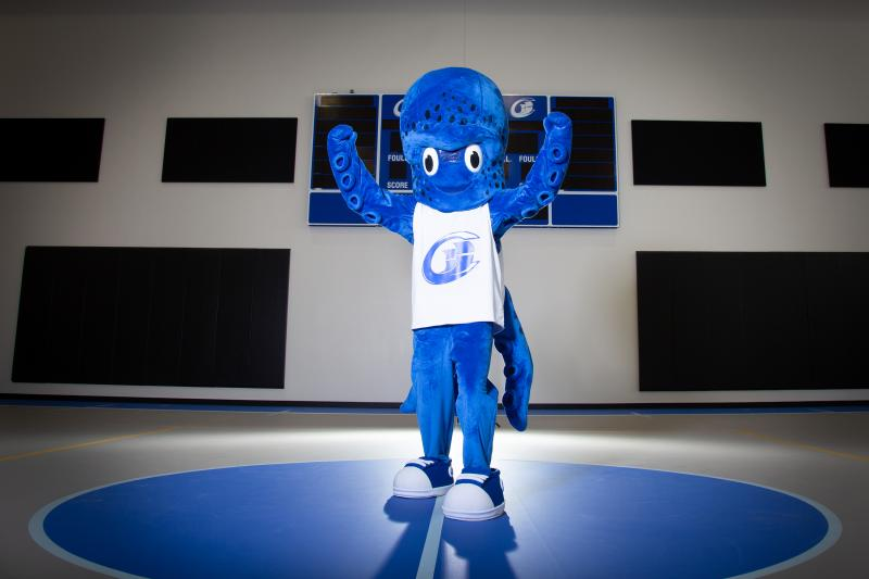 Blue kraken mascot named Percy stands with two tentacles raised up, wearing a white tank top with the Clipper Athletics logo