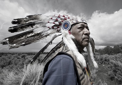 Photo of Native American man with a feather head dress