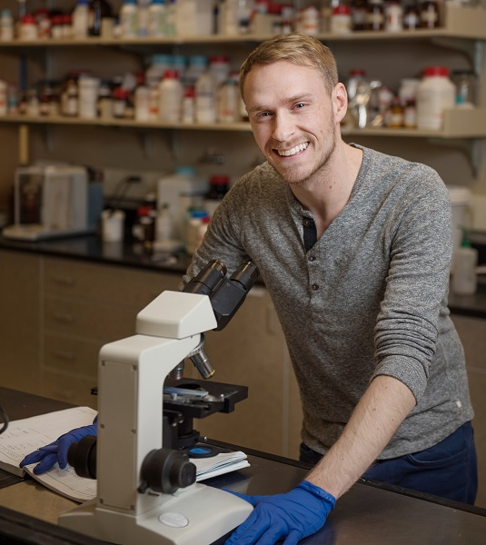 Scott stands in front of a microscope, smiling with blue gloves on