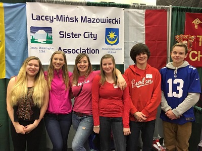 Students smiling in a line in front of a sign that says Lacey Minsk Mazowiecki Sister City Association