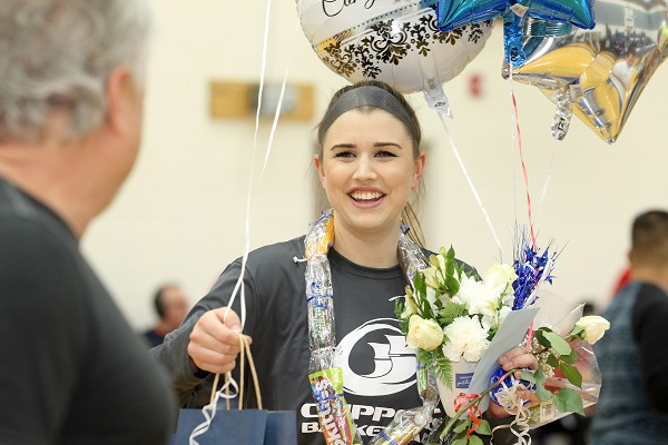 Savannah McGill smiles while holding balloons and flowers during Sophomore Night