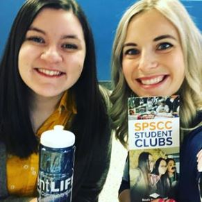 Erika and Kati smile with water bottle and SPSCC student clubs brochure