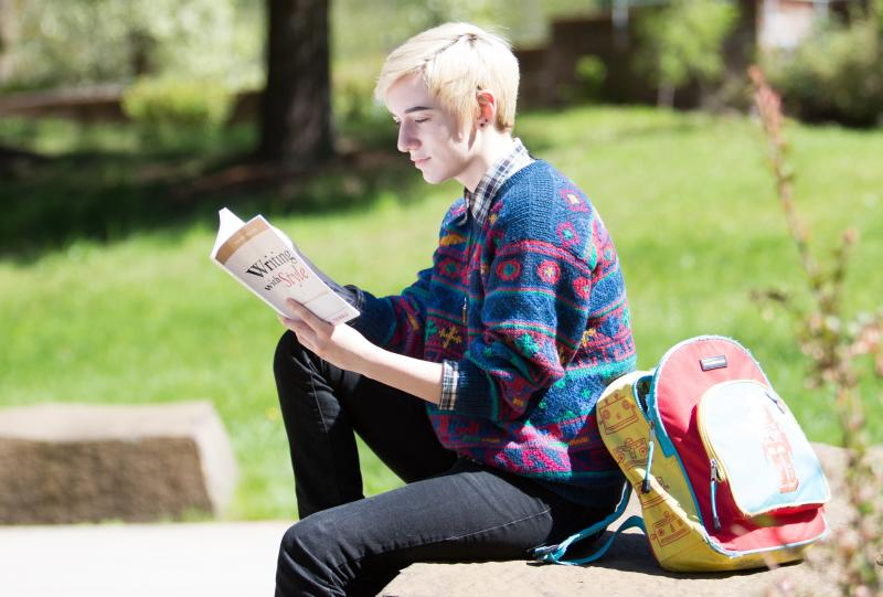 student reading book oustide on a sunny day with colorful backpack