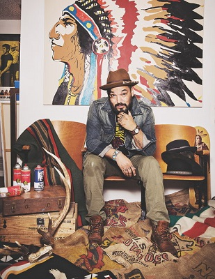 Steven Paul Judd, a Native American man wearing fashionable hat and clothes sitting in front of large Native mural
