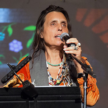 LaDuke speaking at a podium, mic in hand