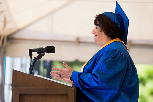Tawni Andrews wearing the traditional blue graduation cap and gown as she gives her speech