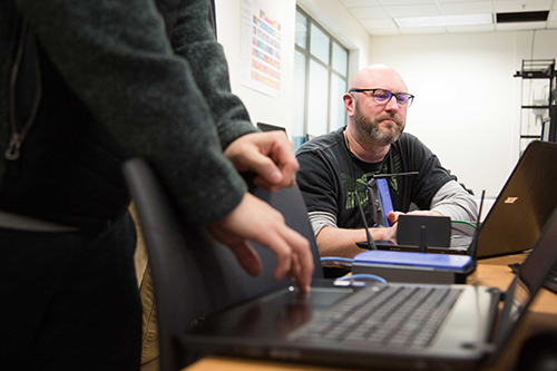 Adult students work with routers in their cybersecurity and network administration class