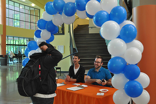 Student Life staff greet students at a Welcome Week table