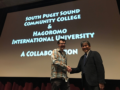 Film professors Gray and Murakami shake hands at A Tale of Two Cities screening